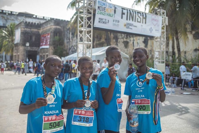 Four young women from Tanzania how off their medals at the end of the Zanzibar Half Marathon, January 2018