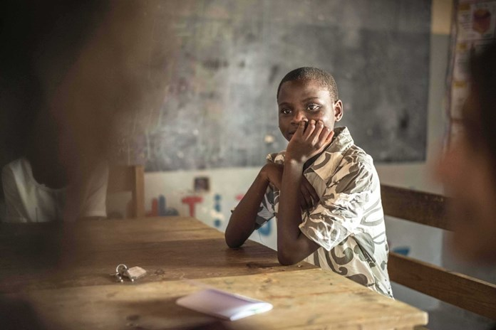 A young Tanzanian girl smiling in her classroom.