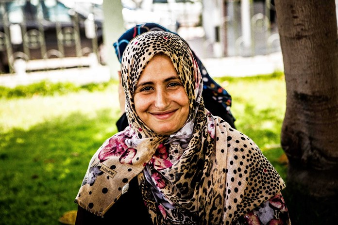 A women sits smiling outside Al Ahli Arab Hospital in Gaza City.