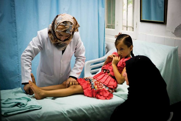 A young girl receiving physiotherapy due to a shrapnel wound at Al Ahli Hospital in Gaza City.