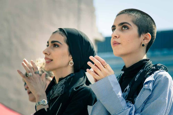 Two Palestinian women clapping.