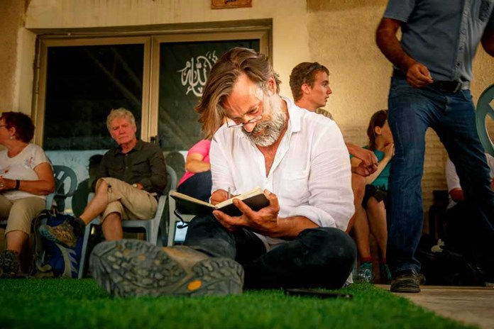 Justin Butcher sitting making notes during Just Walk for his book, 'Walking to Jerusalem' in the West Bank.