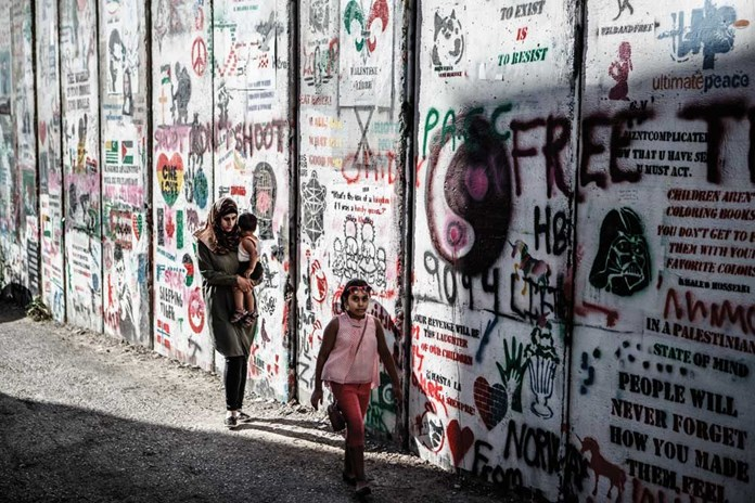 A mother and her children walking along the illegal Israeli Separation Wall that cuts through Bethlehem surrounding it on three sides.