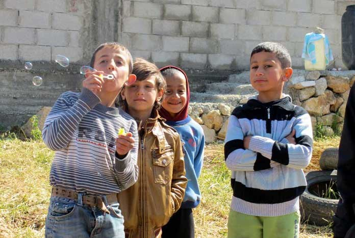 A group of young Palestinian children blowing bubbles and smiling.