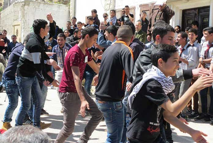 A group of young Palestinian men dancing in the street.