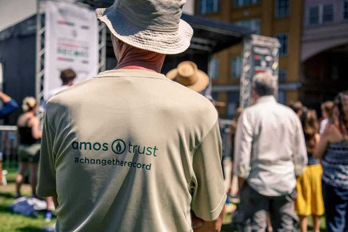 A man standing wearing his Amos Trust 'Change The Record' t-shirt