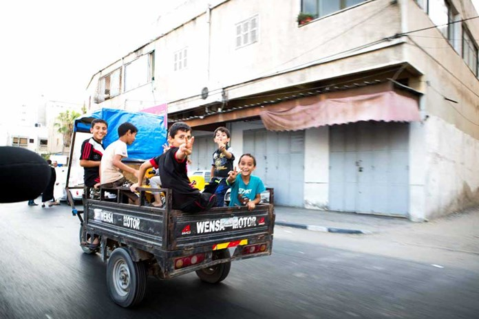 A group of young boys in the back of a small van waving as they ride down a Gazan street.