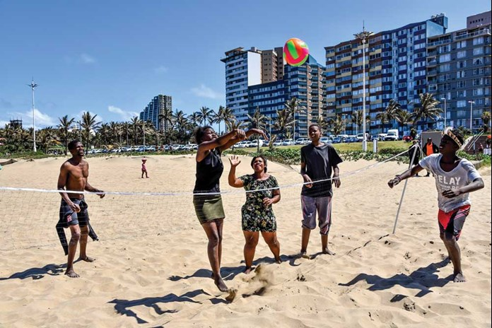 Young people from Umthombo's post-16 programme playing volley ball on the beach.