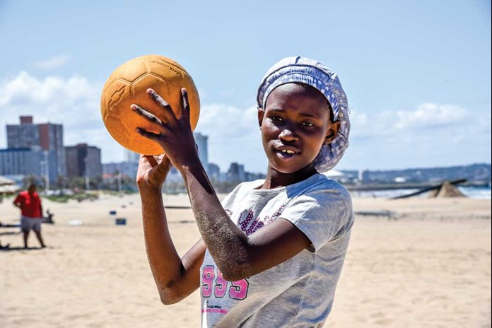 A young women from Umthombo in South Africa playing Volley Ball on the beach in Durban.