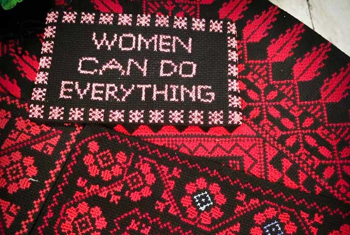 "A piece of red and black crochet that reads. ""Women can do everything."""