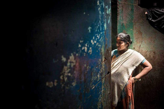 A women from a pavement-dwelling community in India stands in the darkness.