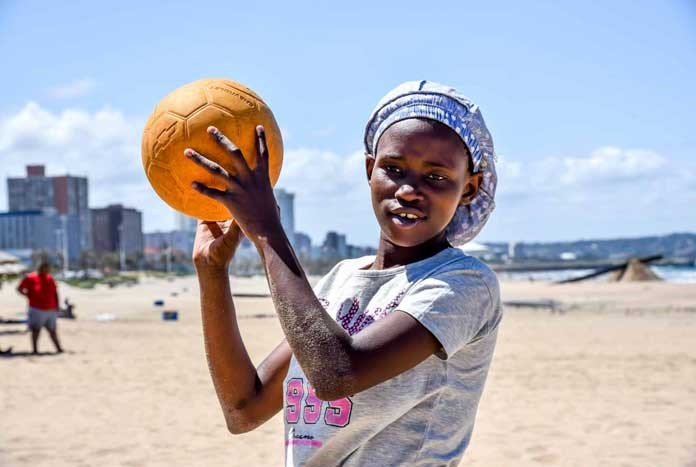 A young women playing beach volleyball on the beach in Durban, South Africa.