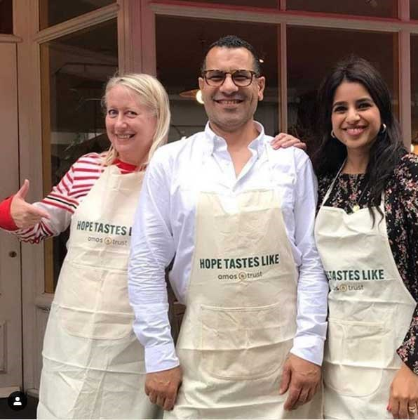 Sami Tamimi and friends wearing Amos Trust 'Hope Tastes Like...' aprons.