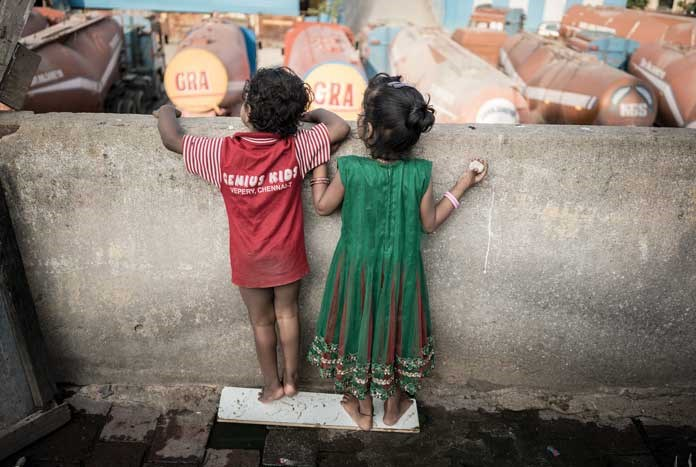 Two young children peering over a wall into a lorry park. Chennai, India — August 2017.