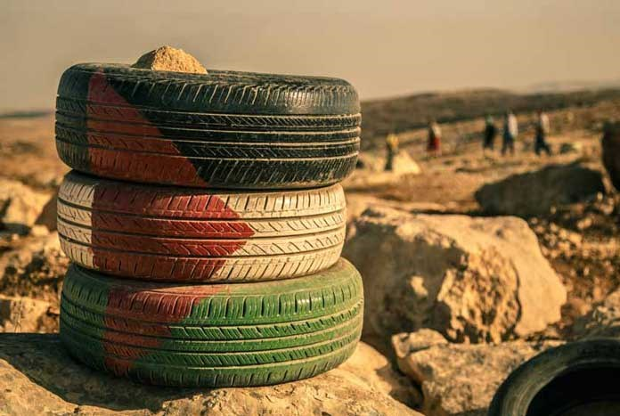 Three old car tyres painted with the Palestinian flag.