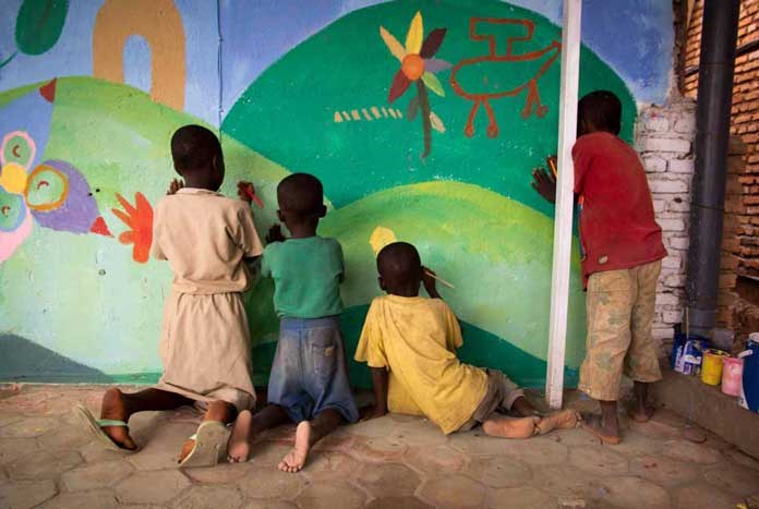 A small group of Burundian children painting a mural on a wall.