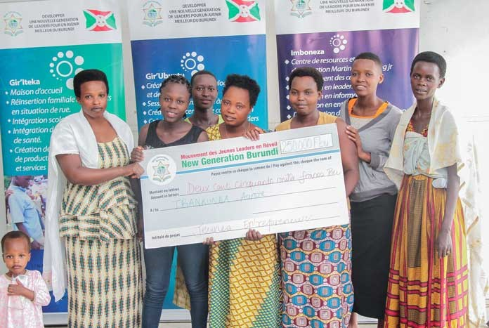 Young women in Burundi holding a large charity cheque.