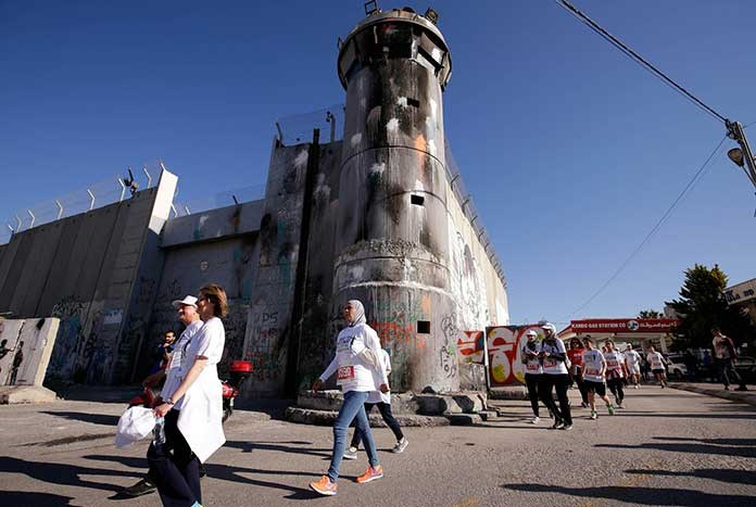 Participants in the Palestine Marathon in Bethlehem run by the 8 metre-high Separation Wall and one of its watch towers.